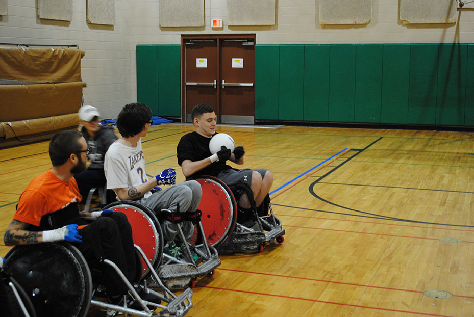 Wheelchair rugby cover art - players playing wheel chair rugby in a gymnasium.